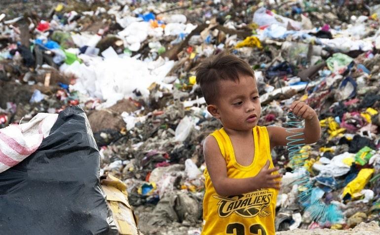 Ребенок на свалке играет с пластиком